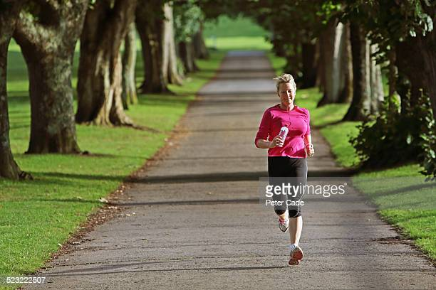 woman in pink top running outside trough landscape