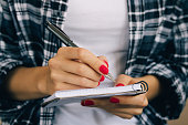 Woman in plaid shirt and a red manicure pen writing in a notebook