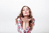 portrait of curly beautiful woman in plaid shirt sending an air kiss