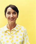 Woman in polka dot shirt standing in front of yellow background