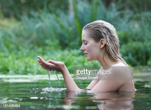 Woman in pond cupping water in hands.