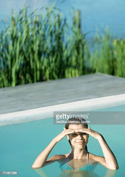 Woman in pool, shading eyes and smiling at camera