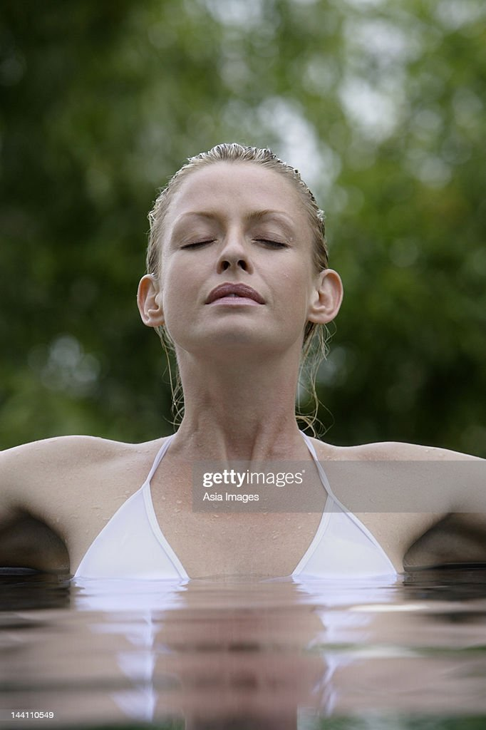 woman in pool surrounded by trees : Stock Photo
