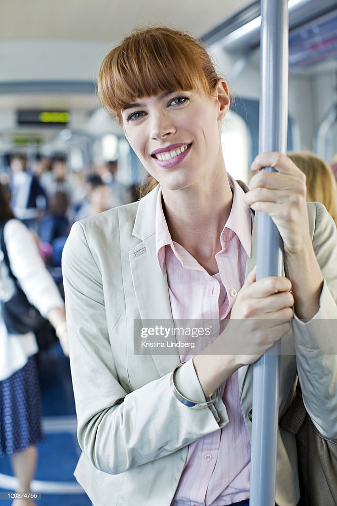 Woman in public transport smiling to camera.