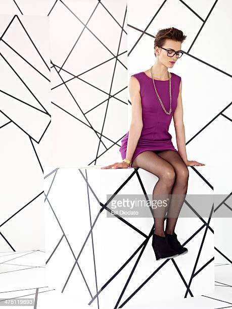 Woman in purple dress sitting in studio