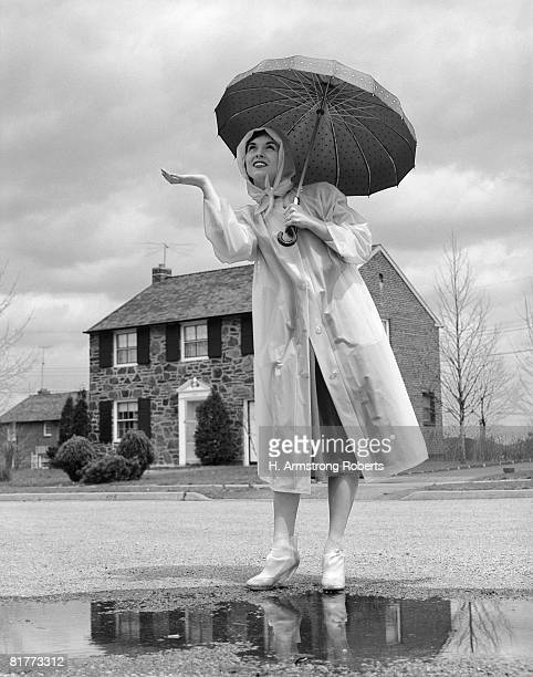 Woman In Raincoat & Rubber Boots Over Pumps With Umbrella Holding Hand Out To Feel For Rain Standing On Suburban Street.