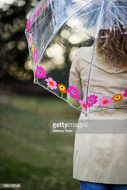 Woman in raincoat with transparent umbrella