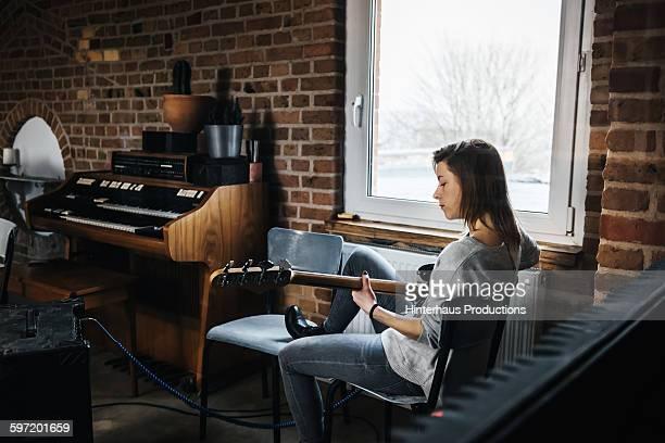 Woman in record studio playing guitar