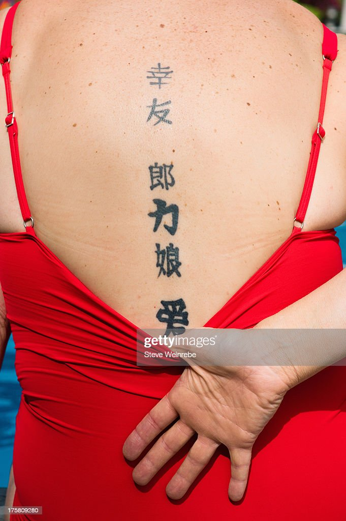 Woman in red bathing suit with tattoos on back
