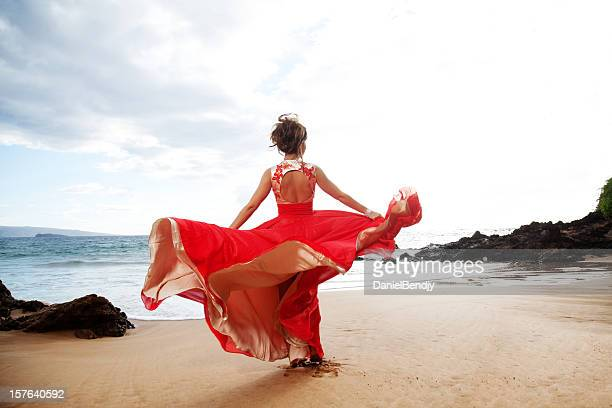 Woman in Red Beautiful Dress Dancing on Beach