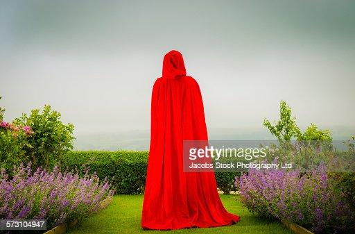 Woman in red cloak standing in garden