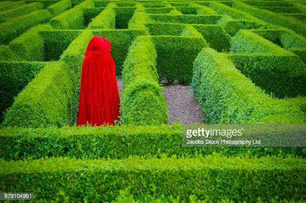 Woman in red cloak walking in hedge maze