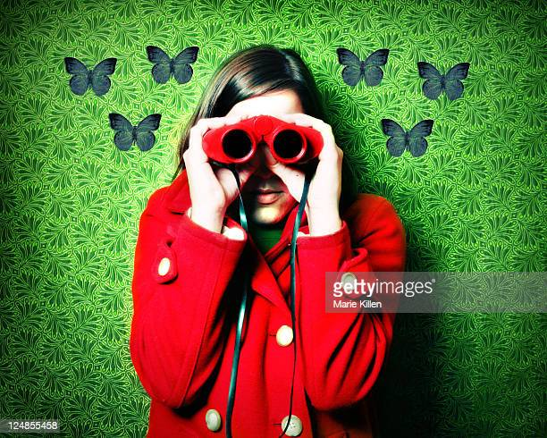 Woman in red coat and red binoculars