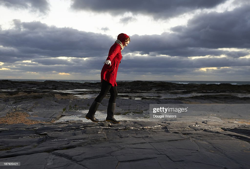 Woman in red coat leaning into wind. : Stock Photo