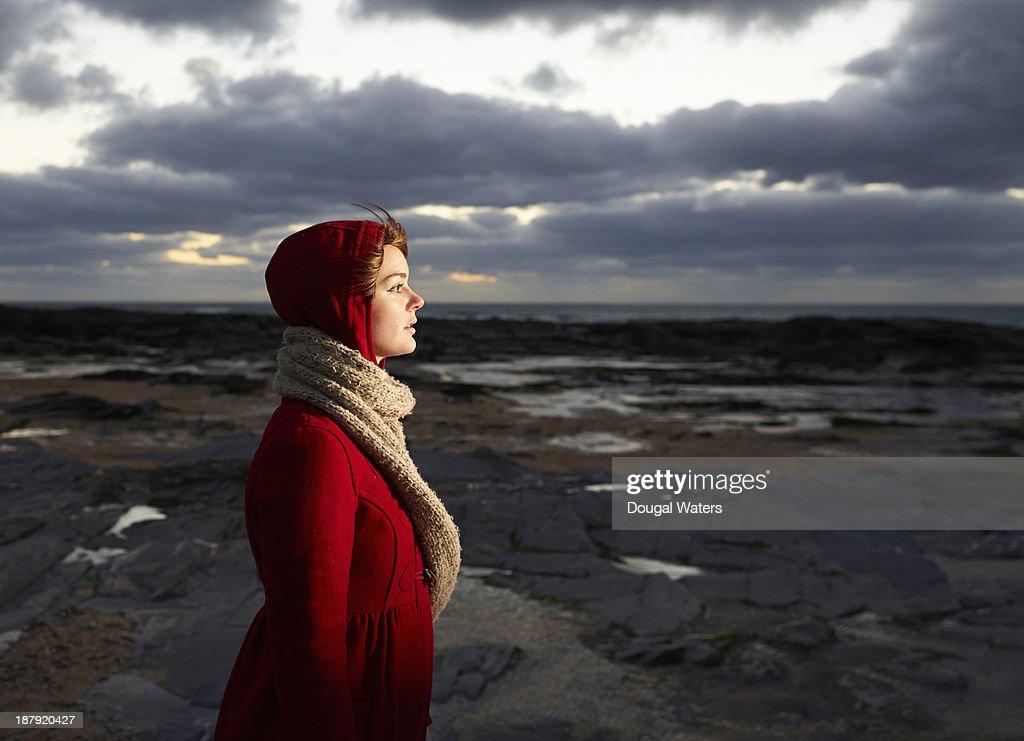 Woman in red coat looking toward light. : Stock Photo