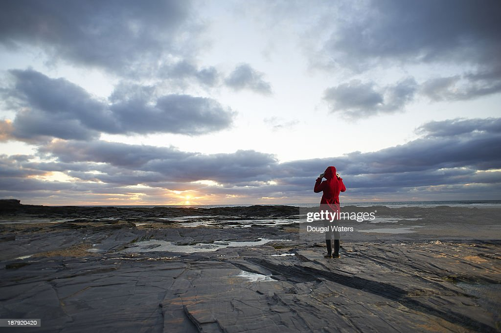 Woman in red coat on coastline at sunset. : Stock Photo