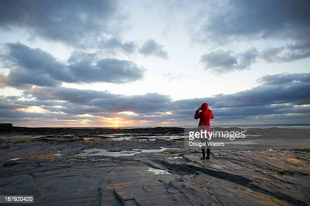Woman in red coat on coastline at sunset.