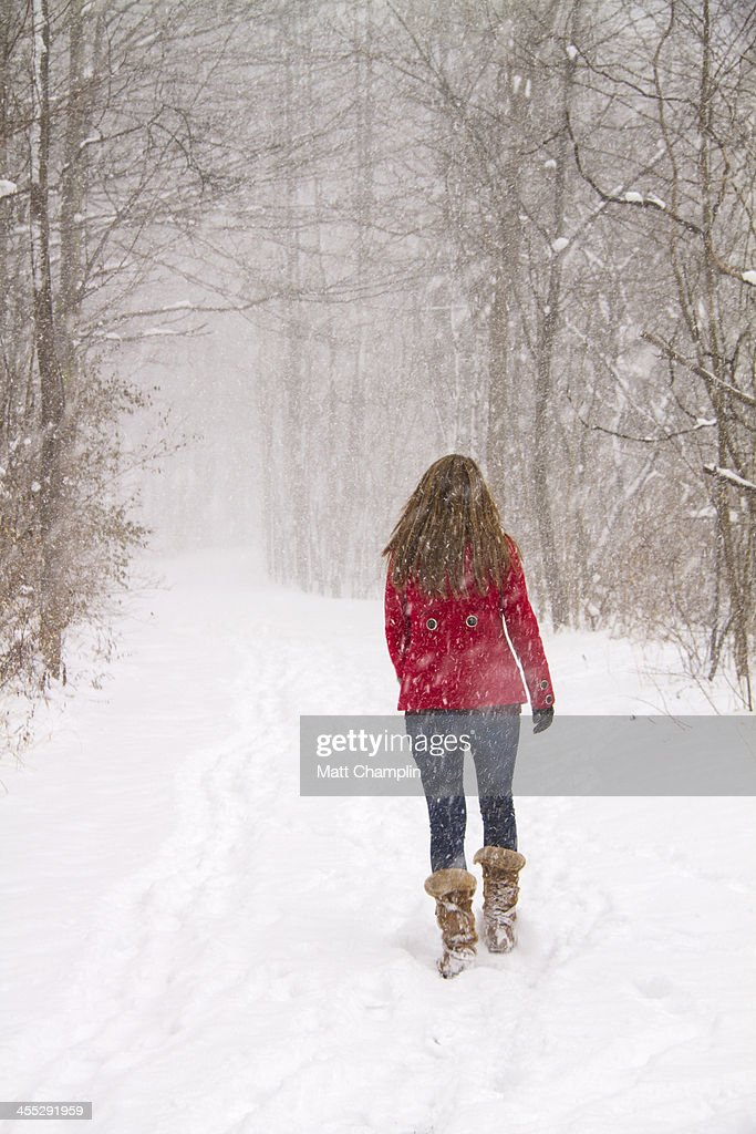 Woman In Red Coat Walking In Snowstorm Stock Photo | Getty Images