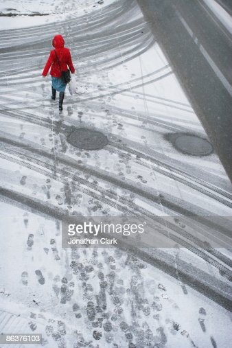 Woman in red coat walking in the snow
