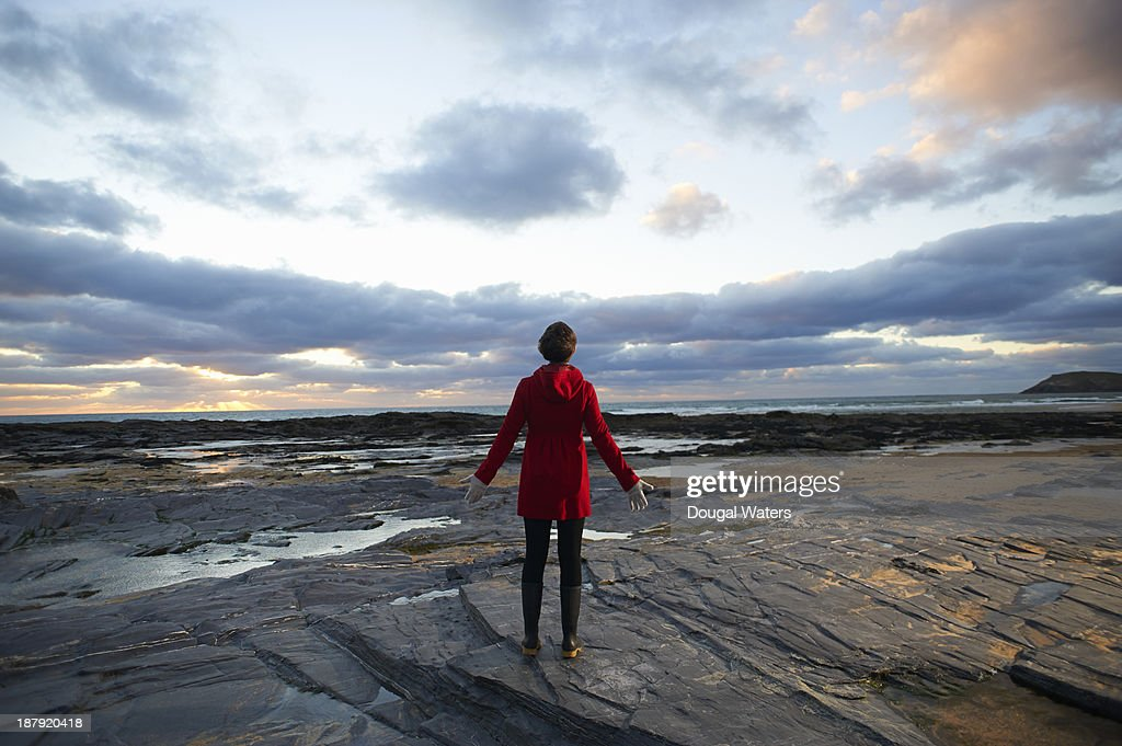 Woman in red coat with arms out on rocky coastline : Stock Photo