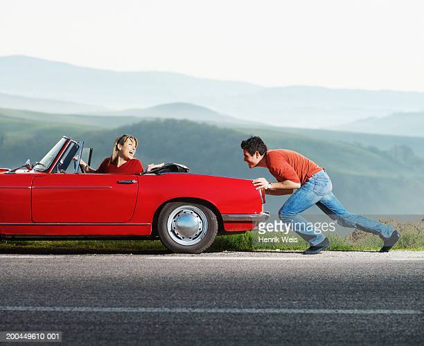 Woman in red convertible car being pushed by man, side view