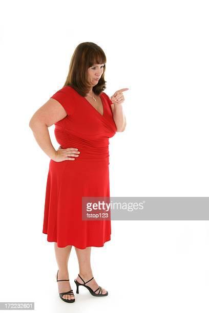 Mujer en vestido rojo y talones señalando con el dedo aislado, fruncir el ceño