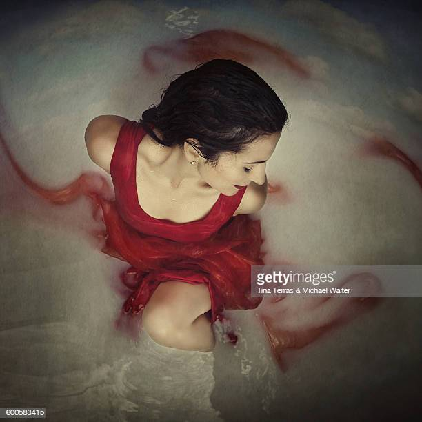 Woman in red dress lies in the water