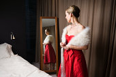 Woman in red dress looking in bedroom mirror