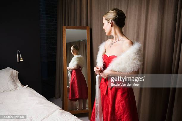 Woman in red dress looking in bedroom mirror