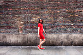 Woman in red dress walking in front of brick wall