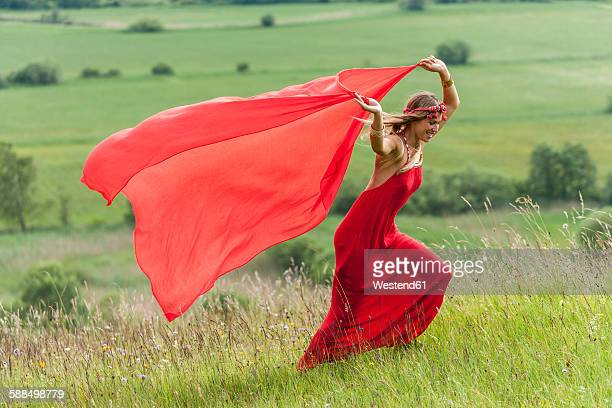 Woman in red dress running on a meadow with red cloth
