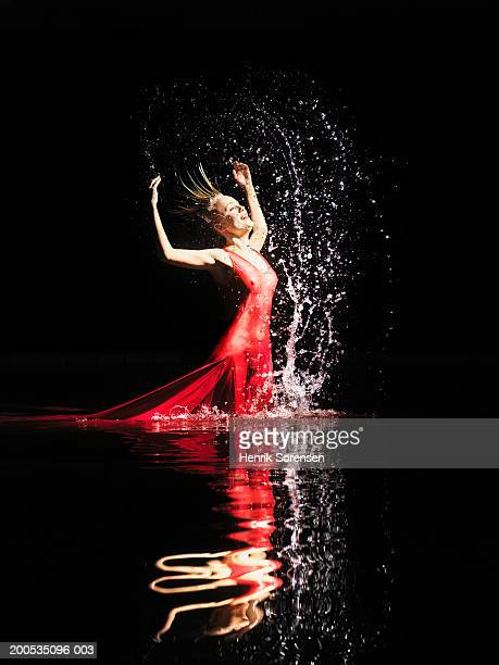Woman in red dress splashing in water against black background