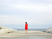 Woman in red dress standing by sea