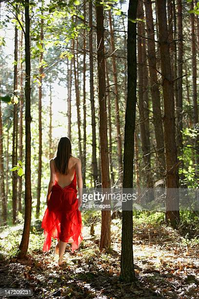Woman in red dress walking through forest