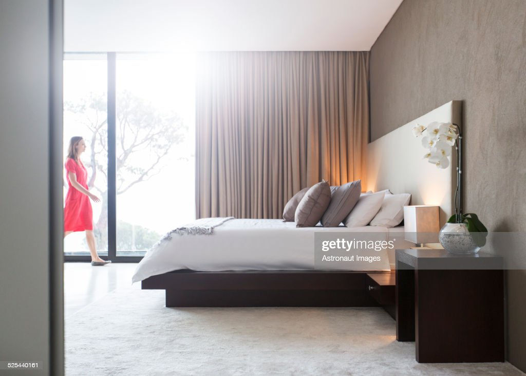 Woman in red dress walking through modern bedroom