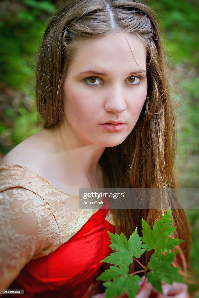 Woman in red fantasy dress holding leaves