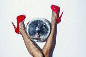 Direct flash detail of woman in red dress, heels, disco ball and champagne bottle lying down on floor.