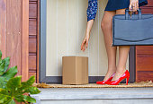 Woman arrives home after work with briefcase to find a delivery parcel at door