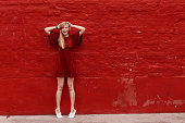 Woman in red dress against red wall, portrait