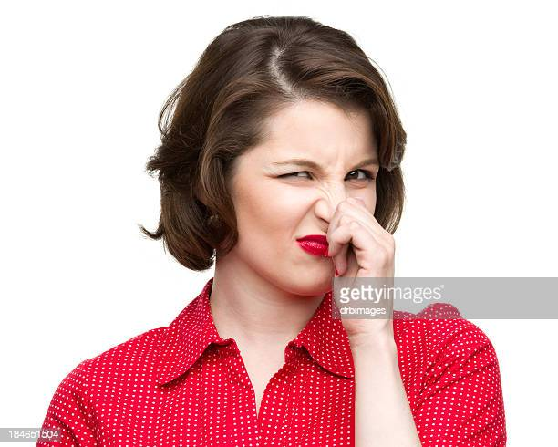 Woman in red pinching her nose showing dislike