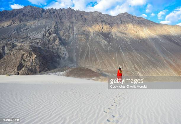 Woman in Red Sharee walking on Sand Dunes of the Cold Desert in Nubra Valley, Leh-Ladakh, India.