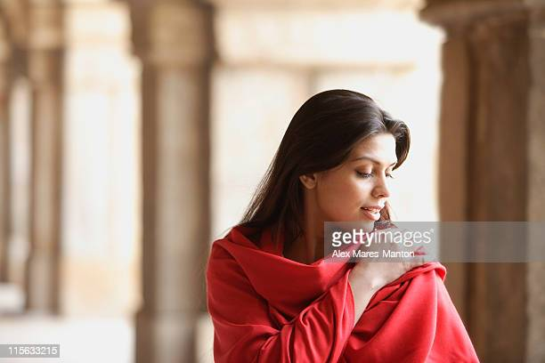 Woman in red shawl, hand on shoulder, in ancient monument