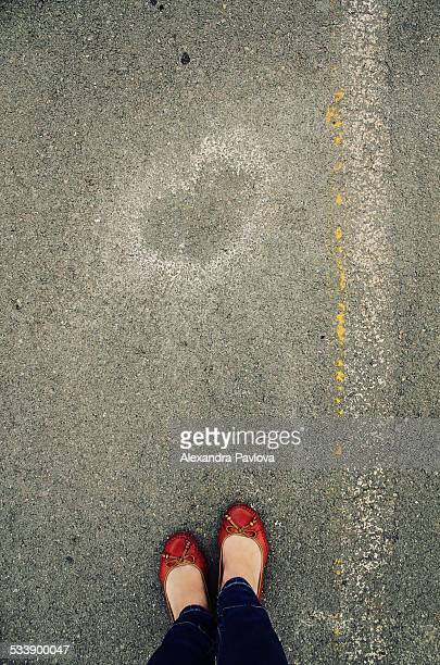 Woman in red shoes standing beside heart of paint