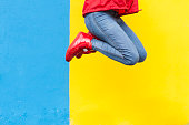 Woman in red sneakers jumping against yellow and blue wall