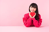 An asian woman in red sweater smiles holding a heart shaped gift box in front of pink background