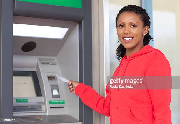 Woman in red urban clothes withdrawing cash.