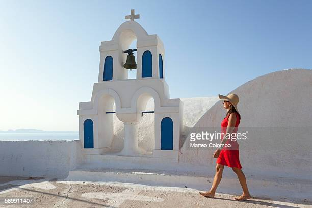 Woman in red walking in greek town, Santorini