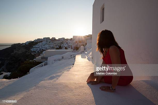 Woman in red watching sunset in Oia, Santorini