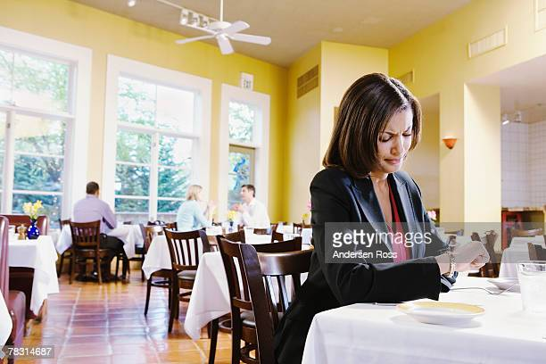 Woman in restaurant checking watch