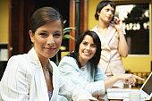 Woman in restaurant smiling, portrait, two women in background